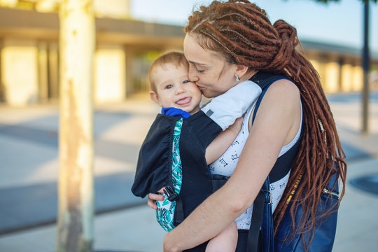 Young happy mom with baby son in ergo backpack travel together. The dark wall on the background. The concept of modern parents