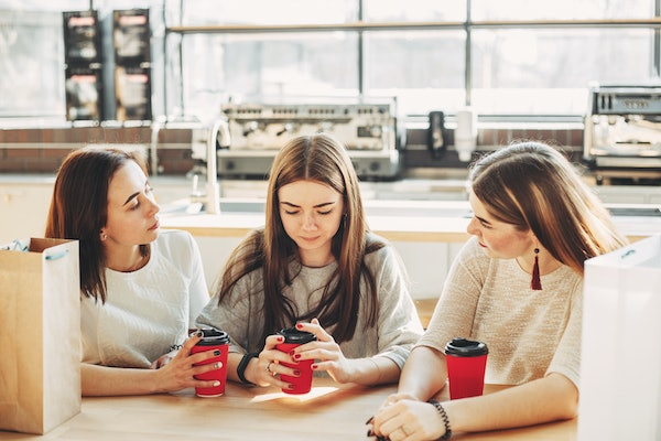 Best friends trying to comfort and cheer up young depressed woman after break up sitting at the table at cafe. Three women drink coffee at the mall