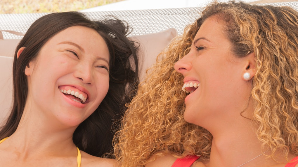 Close-up of two lovely, smiling girls, one asiatic and the other blonde - Vacation concept