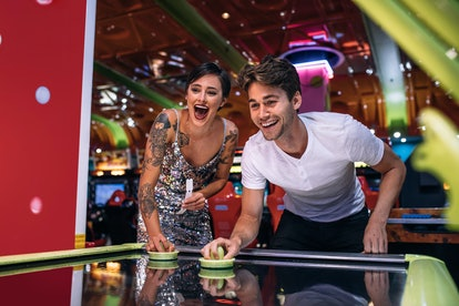 Couple playing air hockey game holding strikers at a gaming parlour. Excited man and woman having fun playing games at a gaming arcade.
