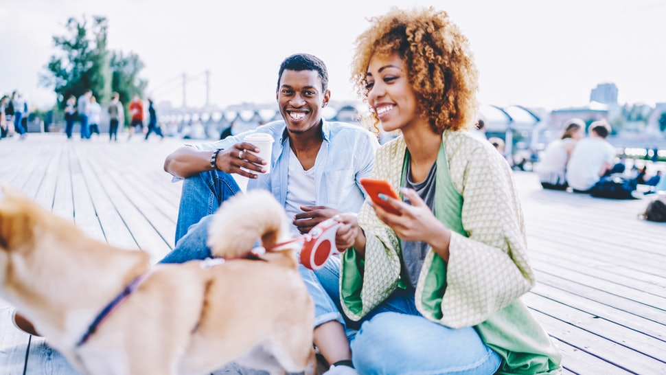 Portrait of african american hipster guy with coffee to go smiling at camera while spending sunny day with lovely girlfriend and dog in urban setting.Happy couple in love enjoying free time together