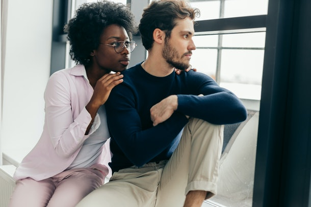 Sad disappointed european man can not forgive his african girlfriend infidelity, the girl is sitting next to man having apologetic guilty look, trying to make peace with man. Relationships problems