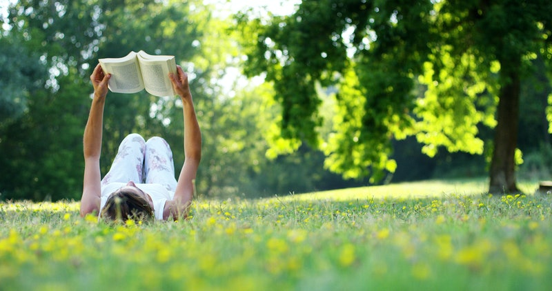 Young woman lying and reading her favorite book on a o green meadow covered with yellow flowers in a nice sunny summer/spring day.Concept of recreation, education and study , curiosity, leisure time