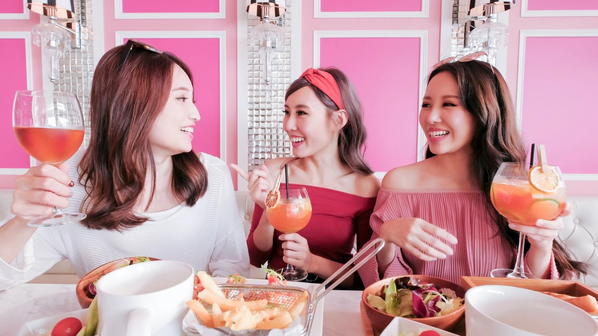 Three friends laugh and hold their cocktails at a pink brunch spot on a sunny morning.
