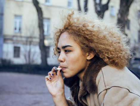 young pretty girl teenage outside smoking cigarette, looking like real junky, social issues concept