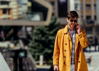 Young businessman walking outdoors while talking on cellphone