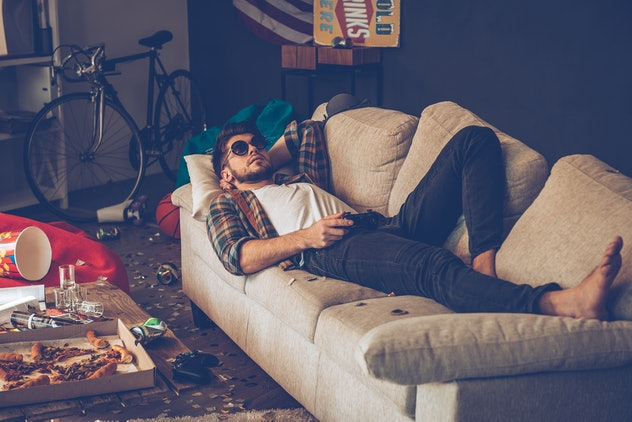Party is over. Young handsome man in sunglasses lying down on sofa with joystick in his hand in messy room after party