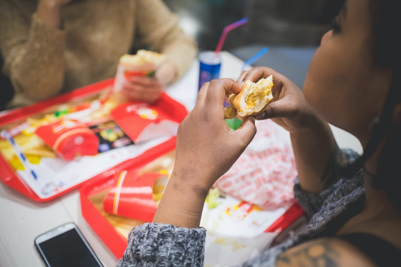 young african woman eating sandwich with friends in fast food – hungry, sharing, joyful