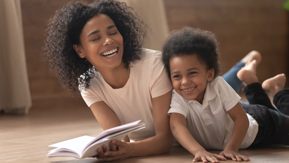 Overjoyed young black mother have fun reading book with cute little son laughing lying on floor together, smiling african American mom laugh enjoy learning spending time with toddler kid at home