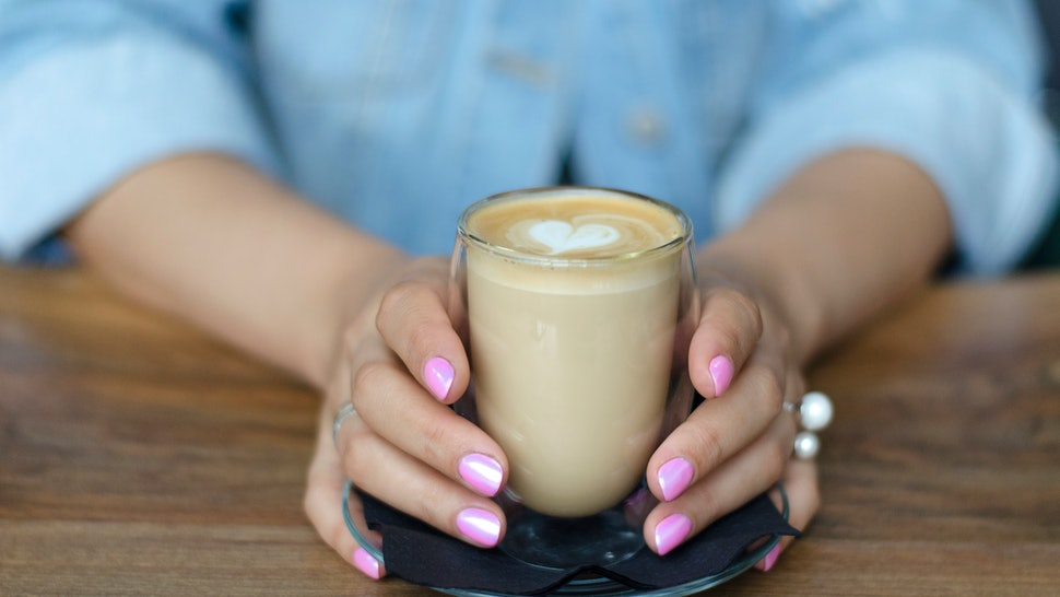 A glass of cappuccino in female hands