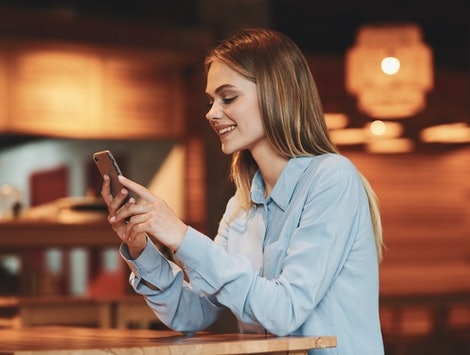 woman with phone smiling at cafe