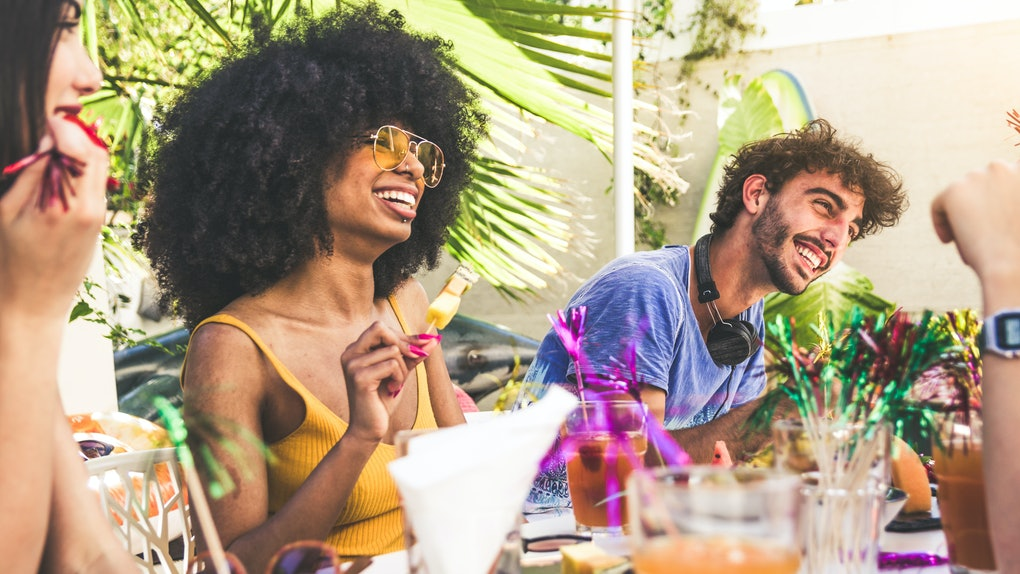 Group of multiracial friends gathered around a table in a garden on a summer day to share meal and laugh togheter