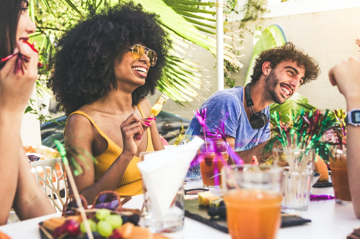 Group of multiracial friends gathered around a table in a garden on a summer day to share meal and l...