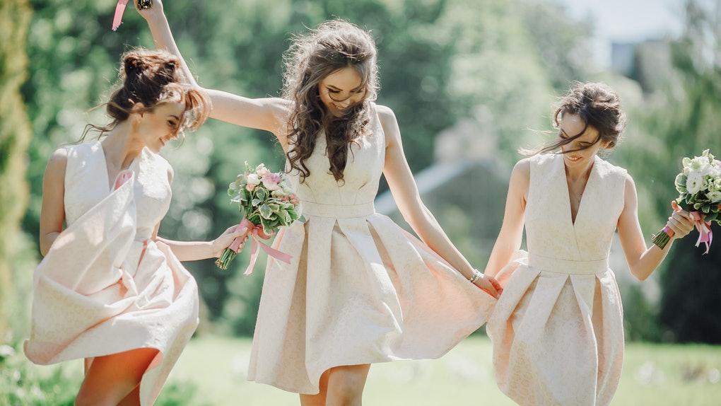 Elegant bridesmaids walk on the green lawn