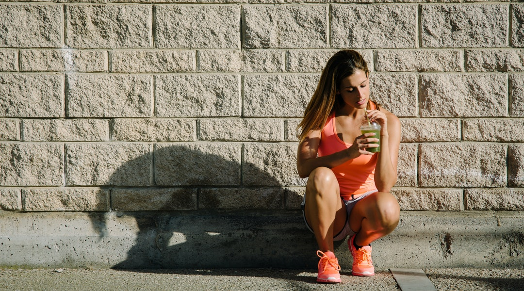 Female athlete taking a workout rest for drinking green detox smoothie.