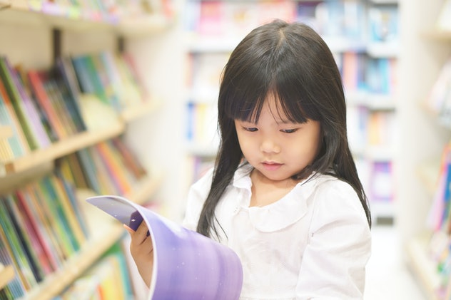 Asian child reading or kid girl happy smile and shopping or choose tale or story book on bookshelf i...