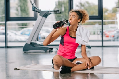 african american female athlete resting and drinking water from sport bottle on fitness mat at gym