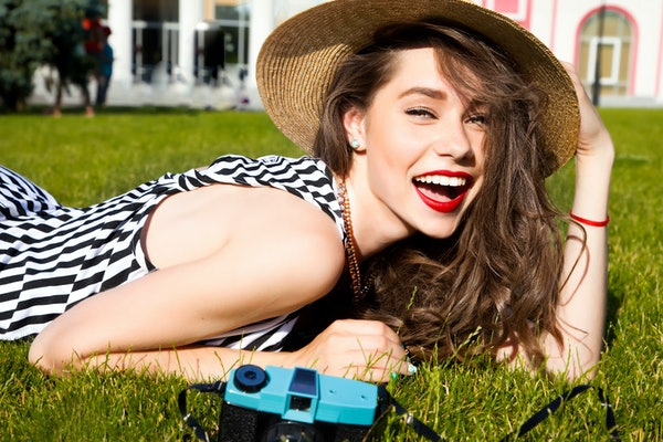 Outdoor lifestyle portrait of stylish girl laughing and smiling holding retro camera.Beautiful sexy woman,evening makeup wearing short dress,summer fall collection perfect in park sun shine,top skirt