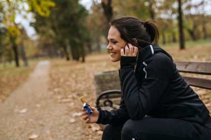 Woman taking break from jogging. sitting on bench and listening to music