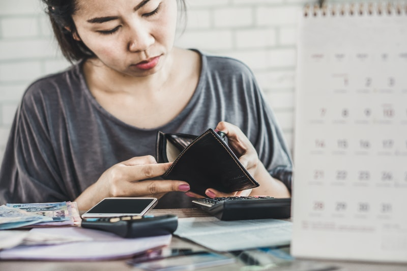 stress Asian woman open empty wallet looking for money for debt