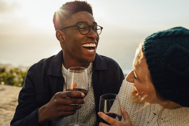 Smiling man and woman with wine glasses sitting in outdoors on a sunny day. Happy couple with red wine enjoying at picnic.