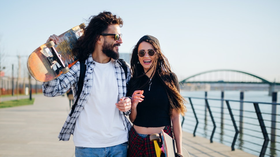 Young man and woman with skateboards, enjoying the sunny day next on a walkway next to the river.