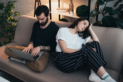 bored woman sitting on couch while man using laptop in living room