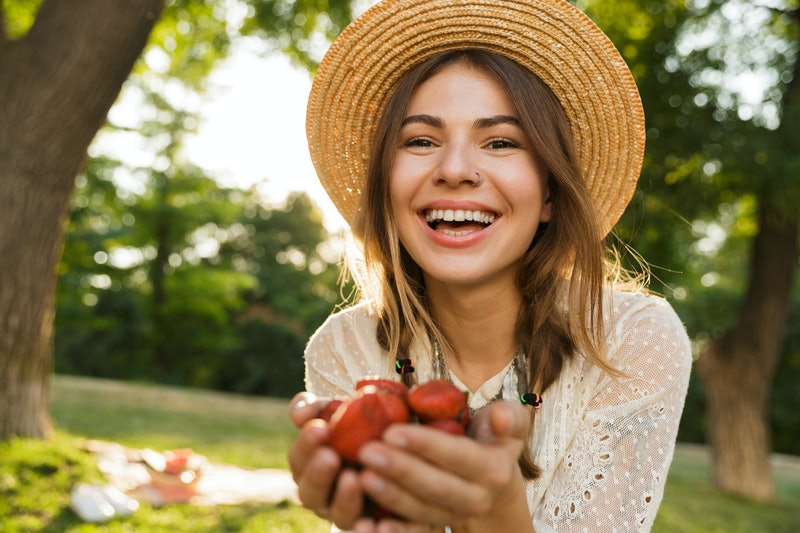 Close up of happy young girl in summer hat spending time at the park, holding heap of strawberries