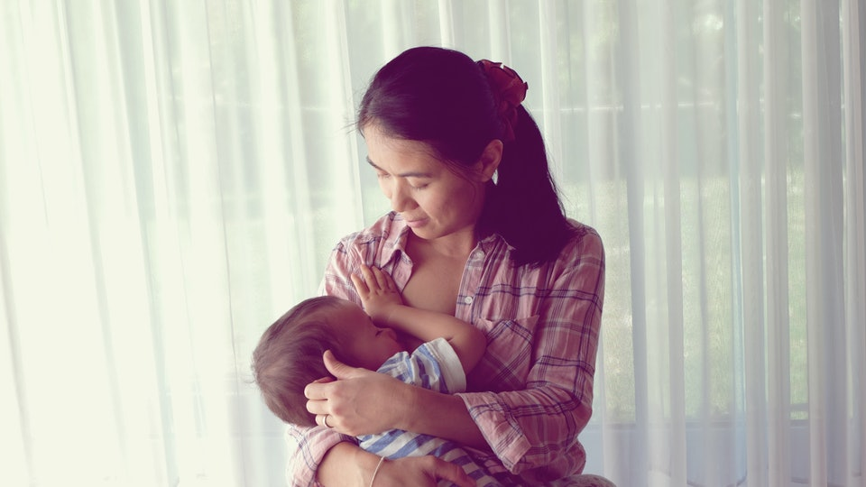 Mother breastfeeding her baby. Mom nursing baby. Vintage photo mom and baby son.