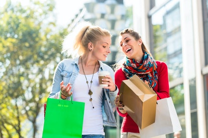 Friends, two women, shopping with bags in city