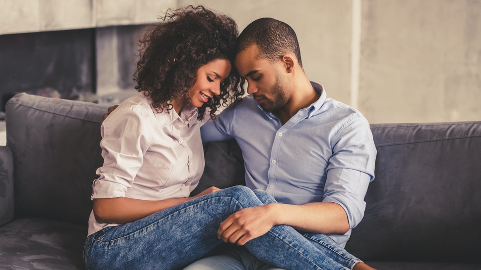 Beautiful young Afro American couple is hugging and smiling while sitting together on couch at home