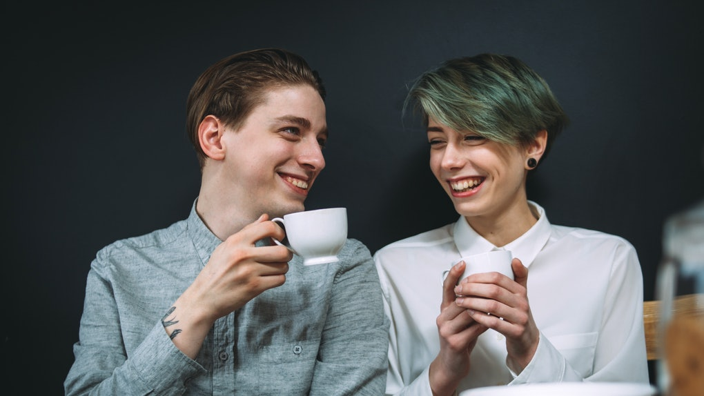 couple love relationship. girlfriend and boyfriend drinking coffee in a bar. talking and laughing on a date