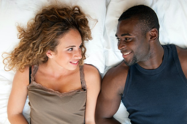 Happy young couple lying in bed looking at each other, top view.