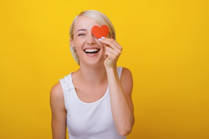 Woman in love, holding a littlle paper heart over eye, standing over yellow background