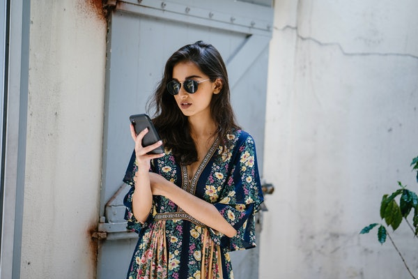 Portrait of a young, attractive and beautiful Indian Asian woman wearing a dress and sunglasses with her smartphone. She looks serious and worried, and is frowning as she looks at her phone.