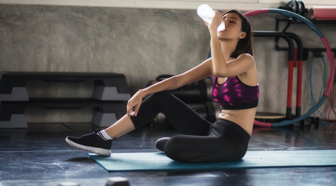 Tired attactive woman break and drink water after perform dumbbell exercise in fitness sport gym with copy space for text. Bodybuilding workout and healthy lifestyle concept.