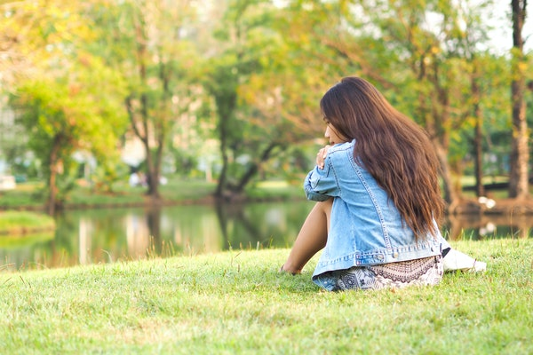Young lonely woman feel sad sitting alone and depressed in the park