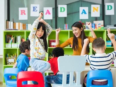 Happy Asian female teacher and mixed race kids in classroom,Kindergarten pre school concept