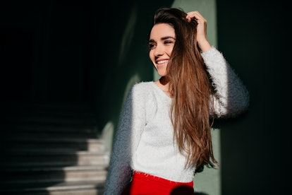 Fashionable girl with long brown hair looking away with cute smile. Indoor portrait of excited caucasian female model standing in the dark near stairs.
