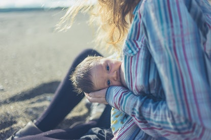 A young mother is breastfeeding her baby on the beach