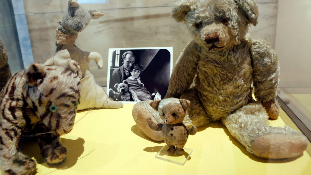 "A. A. Milne, Christopher Robin A photograph of author A. A. Milne with his son Christopher Robin is displayed beside Milne's son Christopher Robin's beloved teddy bear, the inspiration for ""Winne-the-Pooh,"" at the New York Public Library, in New York. The items are part of a library exhibit entitled, ""The ABC of It: Why Children's Books Matter."" The library released a list of 100 great children's books from the last hundred years. ""Winne-the-Pooh,"" is among the recommended titles"