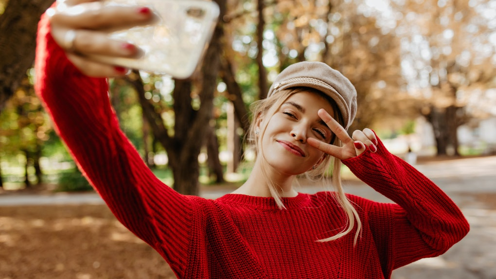 Young woman in nice red pullover make selfie on the park path.