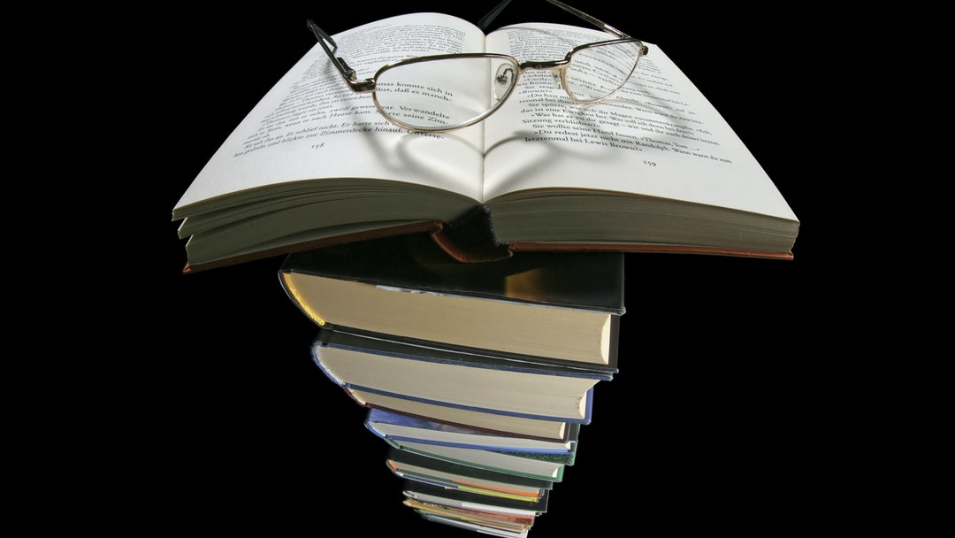 Book, pair of reading glasses, heart-shaped shadow, pile of books