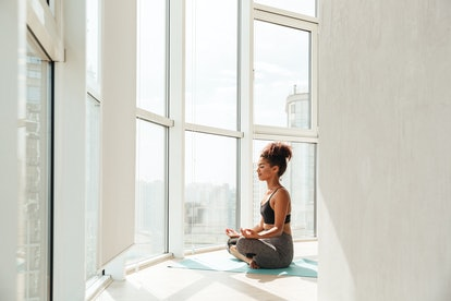 Young african fitness lady in sportswear sitting in lotus pose and looking camera at home