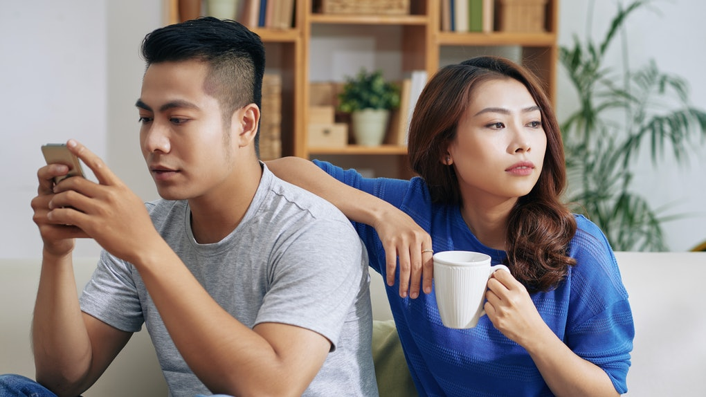 Beautiful Asian woman with coffee leaning on boyfriend absorbed with smartphone and looking bored