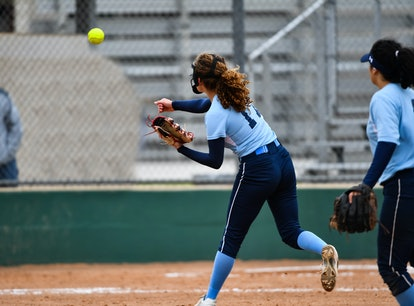 Softball player throwing the ball to first base for an out