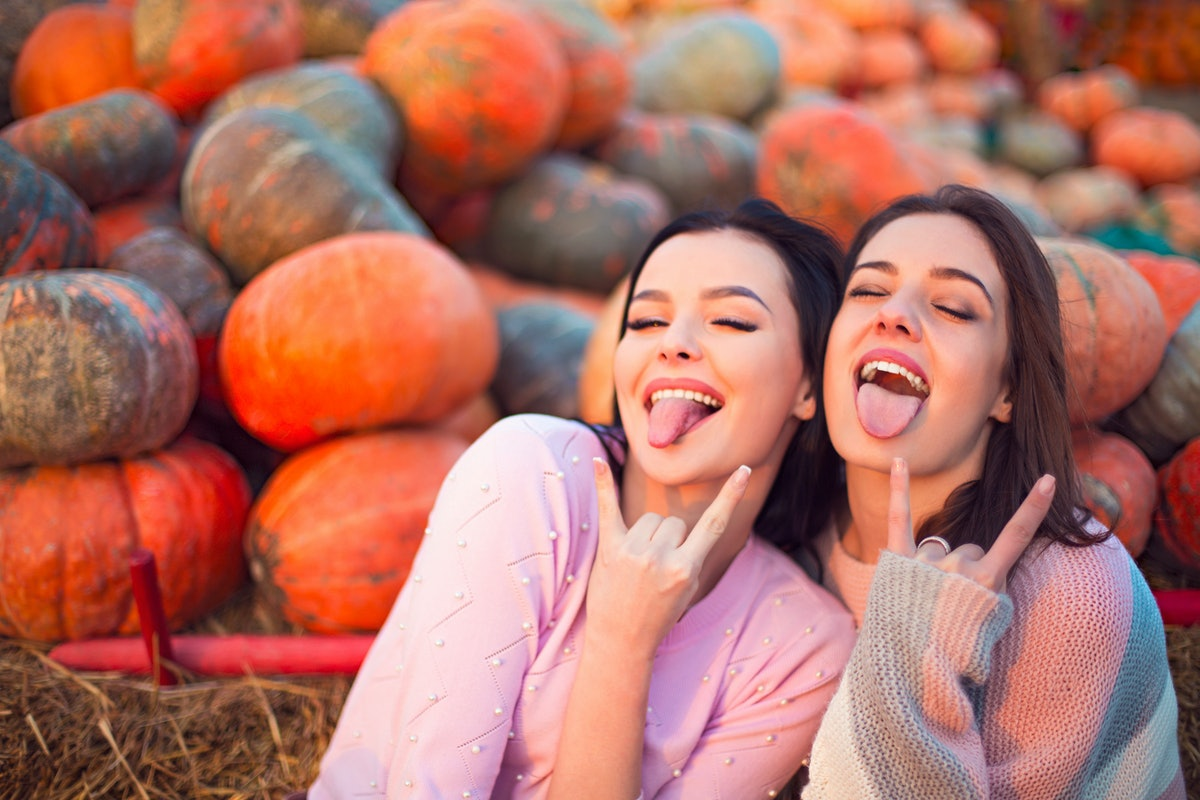 Fashionable beautiful young girlfriends together at the autumn pumpkin patch background. Having fun ...