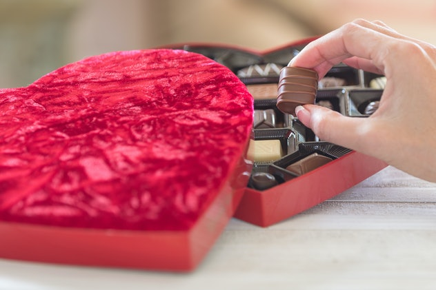 Hand taking a truffle ot of a heart shaped box of chocolates day