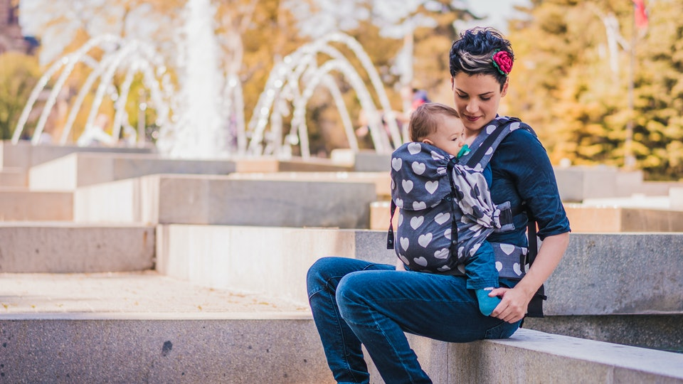 Beautiful happy young mother with baby carrier in park. Mom walking with infant in baby carrier. Happy mother carrying her child by ergonomic baby carrier.