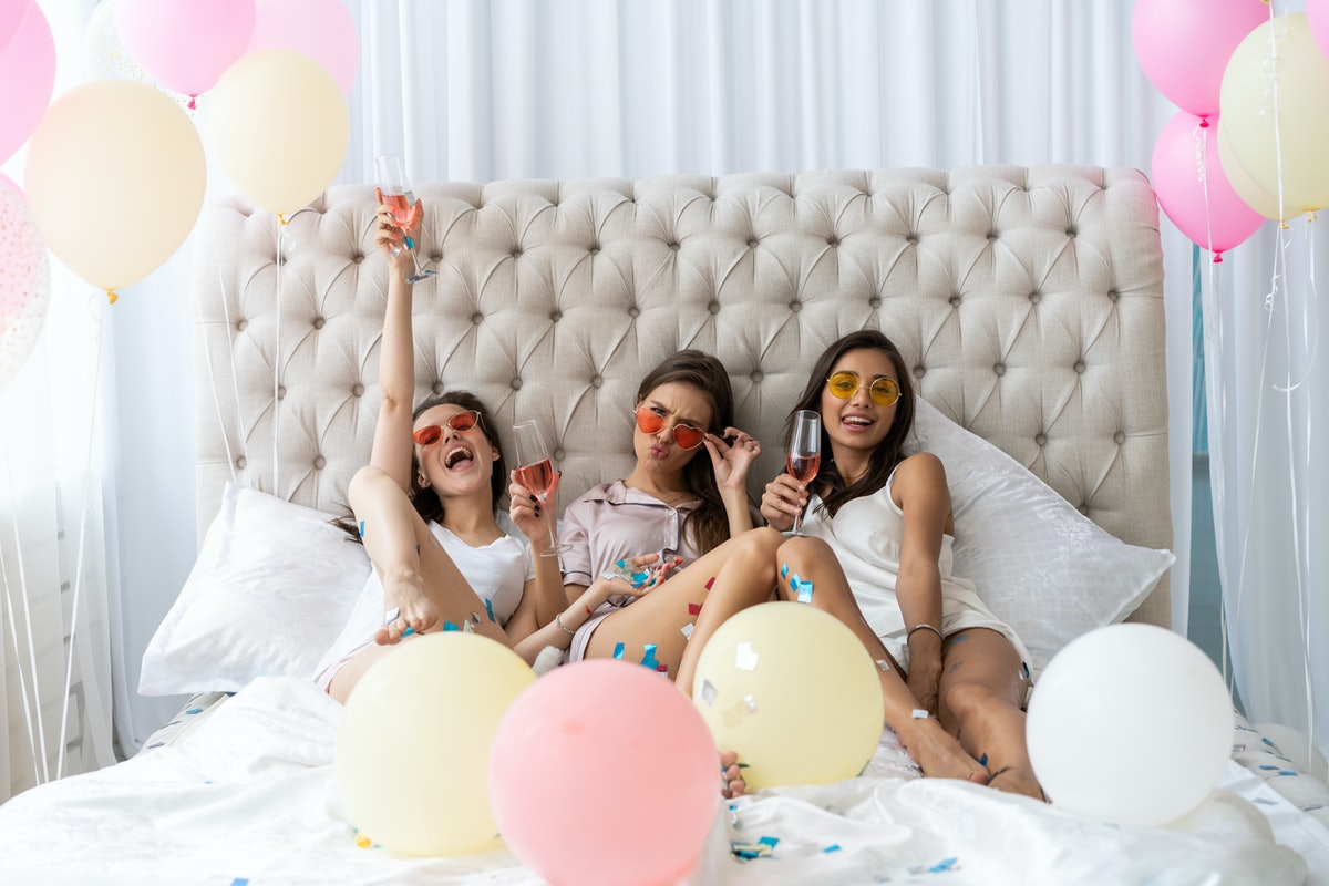 Pajama party. Attractive young smiling women in pajamas drinking champagne while having a slumber pa...